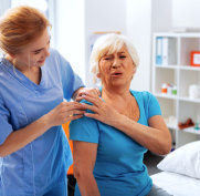 caregiver massaging old woman