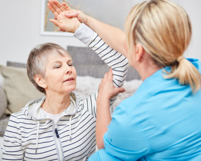 Physiotherapist makes occupational therapy exercise with senior citizen